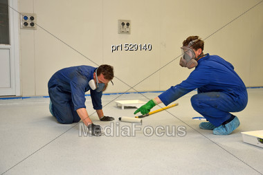 Tradesmen Fix A Problem While Rolling Final Coat Of Clear Epoxy Product On The Floor Of An Industrial Building Stock Photo