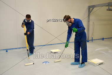 Tradesmen Rolling Final Coat Of Clear Epoxy Product On The Floor Of An Industrial Building Stock Photo