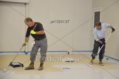 Tradesmen Rolling Final Coat Of Epoxy Product On The Floor Of An Industrial Building Stock Photo