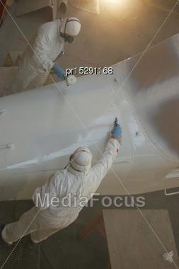 Tradesmen Sprays The Top Of The Nose On A Dornier 228 Aircraft Stock Photo