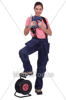 Tradeswoman Holding A Jigsaw With Her Foot Propped On An Extension Reel Stock Photo