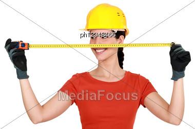 Tradeswoman Using A Measuring Tape Stock Photo