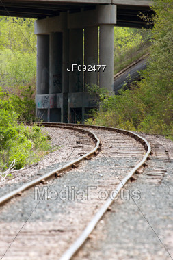 Train Tracks Leading Up To An Overpass Stock Photo