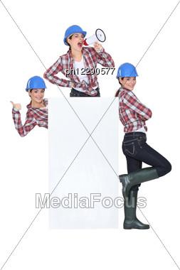 Trio Of Girls Wearing Blue Hard Hat Stock Photo