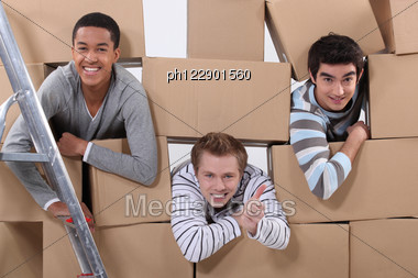 Trio Of Male Flatmates Moving In Stock Photo