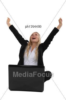Triumphant Businesswoman Sitting At A Laptop Stock Photo