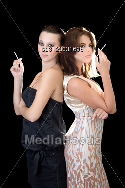 Two Attractive Women Standing Back To Back With Cigarettes Stock Photo