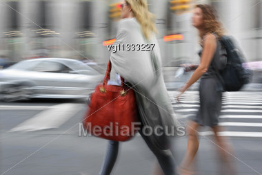 Two Attractive Women Walking On A City Street Holding Bags In Motion Blur, Traffic In The Background Stock Photo