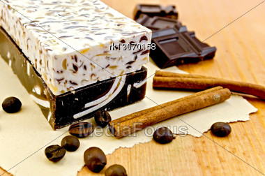 Two Bars Of Beige And Brown Homemade Soap, Chocolate, Cinnamon, Coffee Beans On Old Paper On The Background Of Wooden Boards Stock Photo