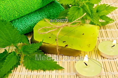 Two Bars Of Green Homemade Soap, Towels, Nettles And Two Candles On The Background Of A Bamboo Napkin Stock Photo