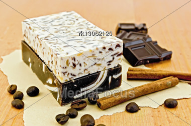 Two Bars Of Homemade Soap Beige And Brown, Chocolate, Cinnamon, Coffee Beans On Old Paper On The Background Of Wooden Boards Stock Photo