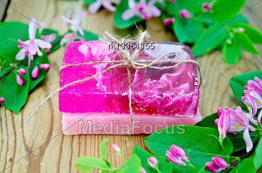 Two Bars Of Soap Homemade Pink, Tied With Twine, Twigs With Leaves And Pink Flowers Of Honeysuckle On A Background Of Wooden Boards Stock Photo