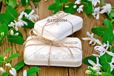 Two Bars Of Soap White, Tied With Twine, Twigs With Leaves And White Flowers Of Honeysuckle On A Background Of Wooden Boards Stock Photo