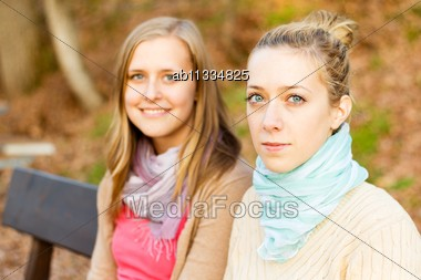 Two Beautiful Young Women Sitting On A Bench In The Park Stock Photo
