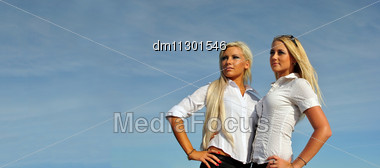 Two Blonde Girls On Sky Background. Perfect For Placing Your Own Advertisements On Stock Photo