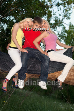 Two Blonde And Young Man Sitting On A Tree Branch Stock Photo