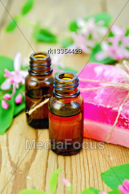 Two Bottles Of Aromatic Oil, Pink Homemade Soap, Branches With Leaves And Pink Flowers Of Honeysuckle On A Background Of Wooden Boards Stock Photo