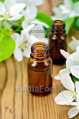 Two Bottles Of Aromatic Oils From Leaves And Flowers Of Apple On The Background Of Wooden Boards Stock Photo