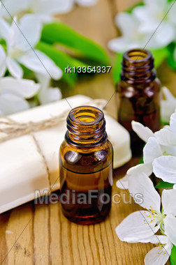 Two Bottles Of Aromatic Oils And White Soap With Flowers Of Apple On A Wooden Boards Background Stock Photo
