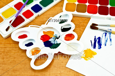 Two Boxes Of Paint, Three Brushes, White Palette In The Shape Of A Butterfly, A Piece Of Paper With A Picture On A Wooden Board Stock Photo