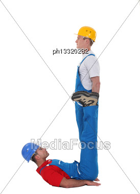 Two Builders Forming The Letter J Stock Photo