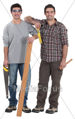 Two Carpenters Stood With Plank Of Wood Stock Photo