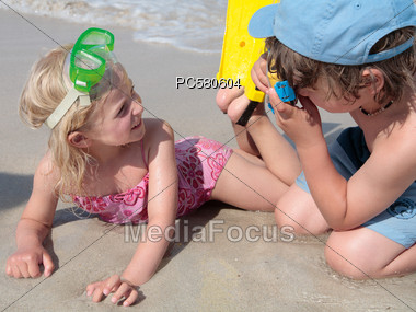 Two Children On The Beach, Young Girl Photographed Stock Photo