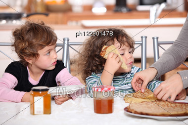 Two Children At Kitchen Table Having Breakfast Stock Photo