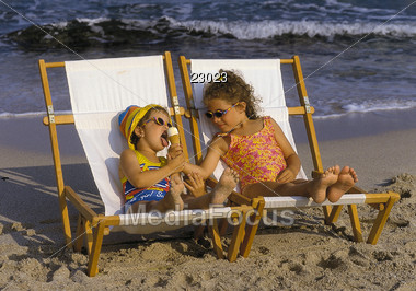 Two children share an ice cream cone at the beach Stock Photo
