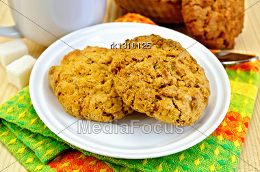 Two Cookies On A White Plate, Spoon, Sugar, White Cup, Basket Weaving, Napkin On A Wooden Board Stock Photo