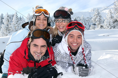 Two Couples Laying In The Snow Stock Photo