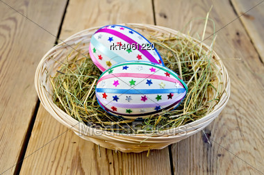 Two Easter Eggs, Decorated With Multicolored Braid And Sparkles In The Hay And A Wicker Basket On A Wooden Boards Background Stock Photo
