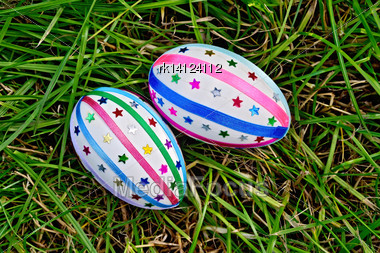 Two Easter Eggs, Decorated With Multicolored Braid And Sparkles As Asterisks On Green Grass Top Stock Photo