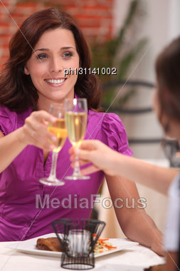 Two Female Friends Drinking Champagne In Restaurant Stock Photo