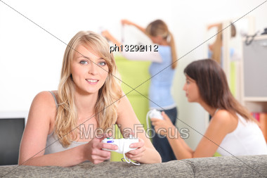 Two Female Friends Playing Video Games With Other Friend In Background Stock Photo