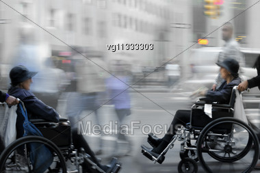 Two Female Handicapped Persons On A Wheelchairs With Assistants , People Walking By Stock Photo