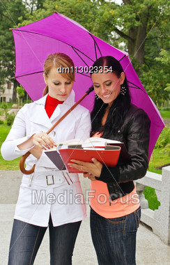 Two Female Students Under Umbrella Outdoors Stock Photo