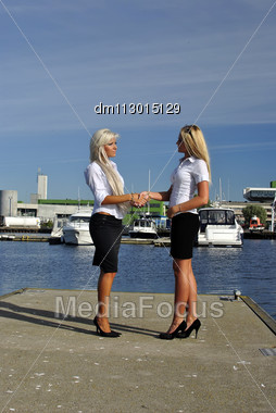 Two Girls Blonde Stand On The Pier And Greet. Handshake Stock Photo