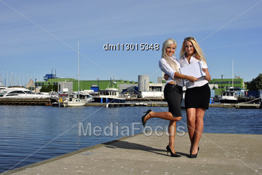 Two Girls With The Documents Standing On The Pier. Boats On The Background Stock Photo