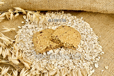Two Halves Of Biscuits Made From Oats And Berries On A Pile Of Oatmeal, Oat Stalks On Burlap And Wooden Board Stock Photo