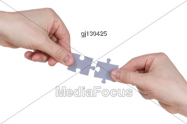two hands connecting puzzle pieces stock photo gj130425