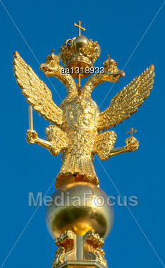 Two-headed Golden Eagle On The Steeple In The Peterhof Palace Against The Blue Sky Stock Photo