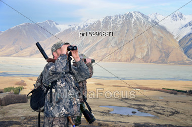 Two Hunters Searching For Himalayan Tahr In The Southern Alps Of New Zealand Stock Photo