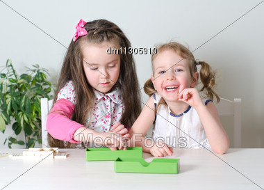 Two Little Girls Playing Domino On The Table Stock Photo