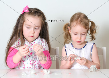 Two Little Girls Sculpting Using Clay Stock Photo