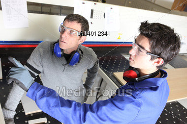 Two Men Operating Industrial Wood Saw Stock Photo