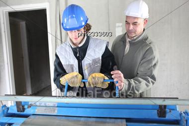 Two Men Operating Machine Than Cuts Sheet Metal Stock Photo
