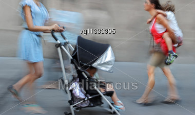 Two Mothers Carrying Toddlers Walking On The Street In Intentional Motion Blur, One Woman Pushing Stroller, Another Woman Holding Toddler On The Back Stock Photo