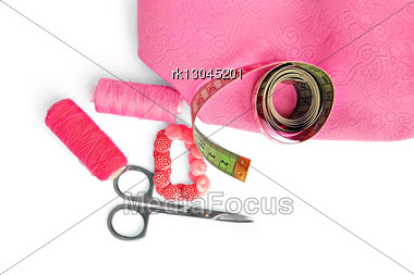 Two Pink Spool Of Thread, Scissors, Pink Buttons, Measuring Tape, Pink Cloth Isolated Stock Photo