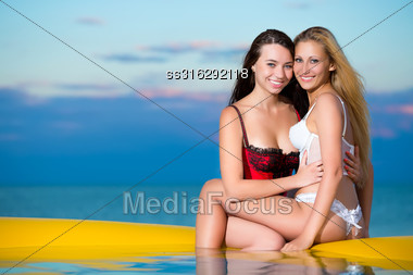 Two Playful Women Hugging Each Other On The Beach At Sunset Stock Photo